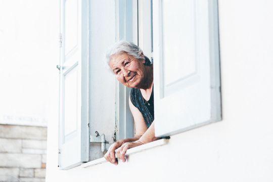 une personne âgée qui regarde par la fenêtre
